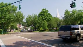 Intersection near Center Green (2 of 2). A municipal building and traffic intersection in a small town stock video footage
