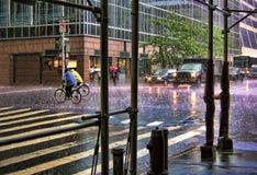 Intersection pluvieuse avec le trafic et des cyclistes photos stock