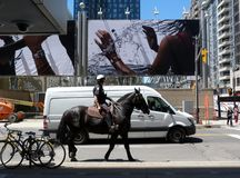 Intersection in Toronto with large street poster and mounted police man stock images