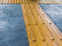 Intersezione di pavimentazione tattile sulla superficie al suolo come orientamento o segnale di pericolo aiutare i pedoni ciechi  immagine stock libera da diritti
