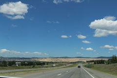Interstate 90, South Dakota. Driving west on Interstate 90 with blue skies and white cumulus clouds. The landscape is typical South Dakota, a mix of rocky yet royalty free stock photography