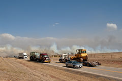 Interstate Traffic Detour. Trucks and Cars detouring around a prairie wildfire that has caused the road behind them to be closed, A truck hauling a grader to Stock Image