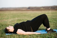 Overweight woman training on mat outdoors. Interval workout, activity, healthy lifestyle, sport, weight loss, tabata. overweight woman training on mat outdoors stock photography