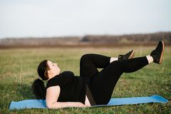 Overweight woman training on mat outdoors. Interval workout, activity, healthy lifestyle, sport, weight loss, tabata. overweight woman training on mat outdoors stock images