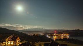 Intervallo di notte con la luna, le stelle, le nuvole, le montagne ed il villaggio vicino al lago archivi video