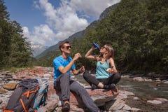 Intervallo di pranzo delle coppie di viaggiatori con zaino e sacco a pelo con landjaeger e pane su un fiume fotografia stock libera da diritti