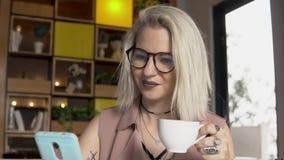 Intervallo per il caffè Femmina che per mezzo dello smartphone mentre bevendo caffè Immagine Stock Libera da Diritti