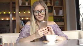 Intervallo per il caffè La donna scrive il messaggio all'amico ed a sorridere video d archivio
