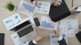 Interventores que comprueban los documentos de negocio de la compañía, trabajando en los ordenadores portátiles, visión superior almacen de video
