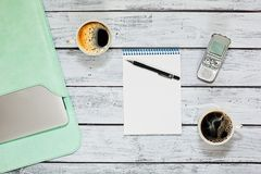 Interview during coffee break. Taking an interview while having a coffee break - top view capture with two cups of coffee on wooden table in loft style, notepad Royalty Free Stock Images
