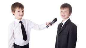 Interview concept - two little boys in business suits with micro Stock Images