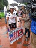 Interview des Frauen-Gegendemonstranten mit Zeichen Lizenzfreie Stockfotografie