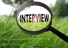 Interview. Magnifying glass with the word interview on grass background. Selective focus Stock Photos