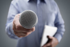 Interview with microphone. Hand holding a microphone conducting a business interview or press conference Royalty Free Stock Photo