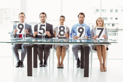 Interview panel holding score cards in office Stock Images