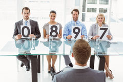 Interview panel holding score cards in office Royalty Free Stock Photos
