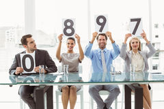 Interview panel holding score cards in office Royalty Free Stock Image