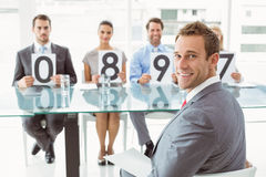 Interview panel holding score cards in office Stock Photography