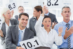 Interview panel holding score cards in office Stock Photos