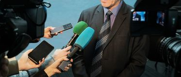 Interview, report, media. Abstract man in a suit and tie speaks to reporters and video cameras. Female hands hold microphones, royalty free stock photo