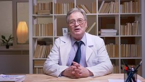 Interview of senior doctor in white coat talking into camera on book shelves background.