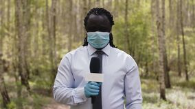 Interview shot. African reporter with face medical mask and gloves in the forest
