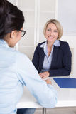 Interview with two businesswomen at desk at office. Interview at office between two business women Stock Image