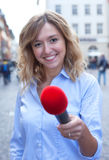 Interview of a young woman with blond hair in the city. With street and buildings in the background Stock Images