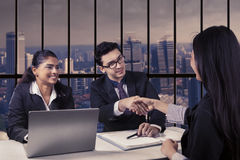 Interviewer shaking hands with new employee. Portrait of male interviewer and his partner shaking hands with new female employee in the office Stock Photos