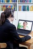 Intervju kvinnahörlurar med mikrofonför online-jobb royaltyfri fotografi