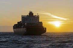 Intestazione della nave porta-container verso il tramonto Fotografie Stock Libere da Diritti