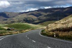 Intestazione della strada attraverso il passaggio di Lindis, Nuova Zelanda fotografie stock libere da diritti