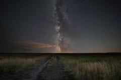 Intestazione della strada non asfaltata verso la galassia della Via Lattea immagini stock