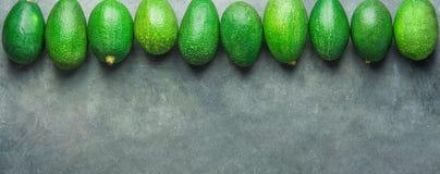 Intestazione lunga dell'insegna Il mazzo di avocado crudi maturi sistemati in tomaia rasenta il fondo di pietra scuro Spazio dell fotografia stock libera da diritti