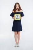 Intégral de la jeune femme étonnée tenant et tenant l'horloge Photo stock