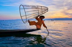 Portrait of fisherman, Inle Lake, Myanmar. INTHA, MYANMAR - FEBRUARY 18, 2018: The portrait of fisherman in traditional attire with conical net on sunset on Inle Royalty Free Stock Photo