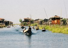 Intha people on Inle lake. Scenic view of ethnic Intha boat people on Inle lake with stilt house in background, Myanmar royalty free stock photo