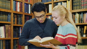 Intilligentny Korean man and Caucasian woman standing together watching the book in the library. stock footage