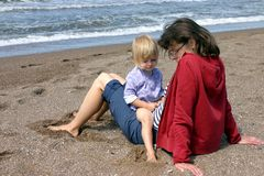Intimacy. Mother and her little daughter sitting on the beach Royalty Free Stock Photos
