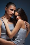 Intimacy of the couple. Intimacy moment of a couple hugging and hugging wearing grey clothes on dark background Royalty Free Stock Images
