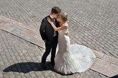 Intimacy & Tension. A wedding couple stands on a paved street with a diagonal line of other stones which creates tension in the picture where her mermaid dress Stock Photos