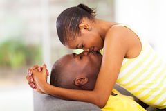 Intimate african couple. Young intimate african american couple kissing and flirting Royalty Free Stock Photography