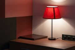 Bedside table on which lie the leather folder of the menu, do not disturb the sign and the lamp with a textile lampshade. Stock Image