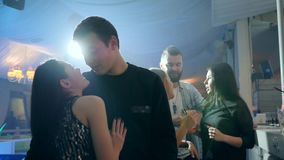 Intimate atmosphere, romantic couple stands close together and kissing on background of bright lights in club. Intimate atmosphere, romantic couple stands close stock video footage