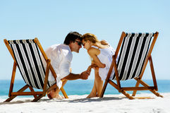 Intimate beach couple. Young couple at the beach in summer share an intimate moment of love and affection Royalty Free Stock Image