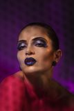 Intimate beauty. Beauty image of a woman with strong purple makeup and background shot through grid to add intimacy look Stock Images