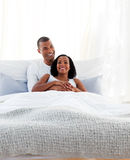 Intimate couple cuddling lying on their bed. Concept of love stock photography