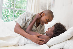 Intimate couple cuddling lying on their bed Stock Photography