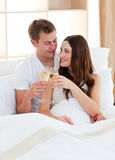 Intimate couple drinking champagne lying in bed. At home Stock Photo