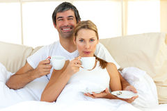 Intimate couple drinking coffee lying in the bed Royalty Free Stock Photography